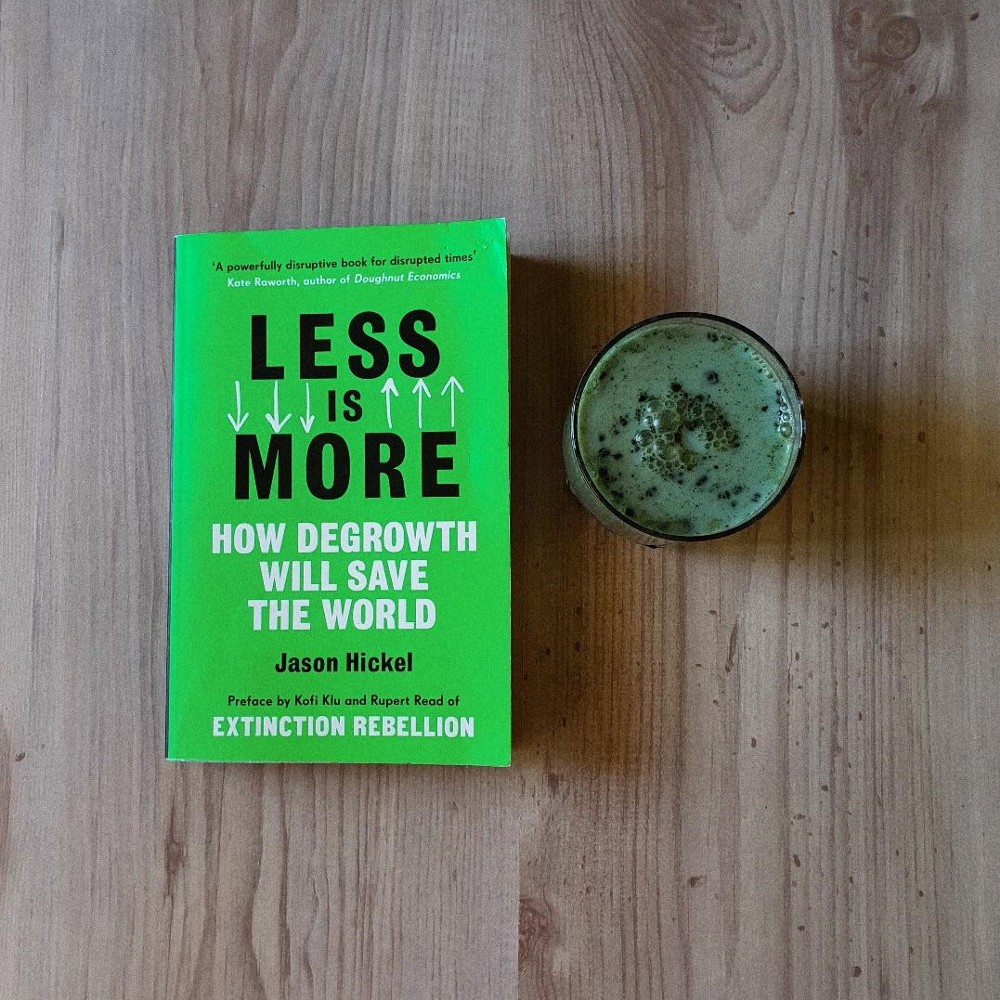 The book Less Is More by Jason Hickel and a matacha latte